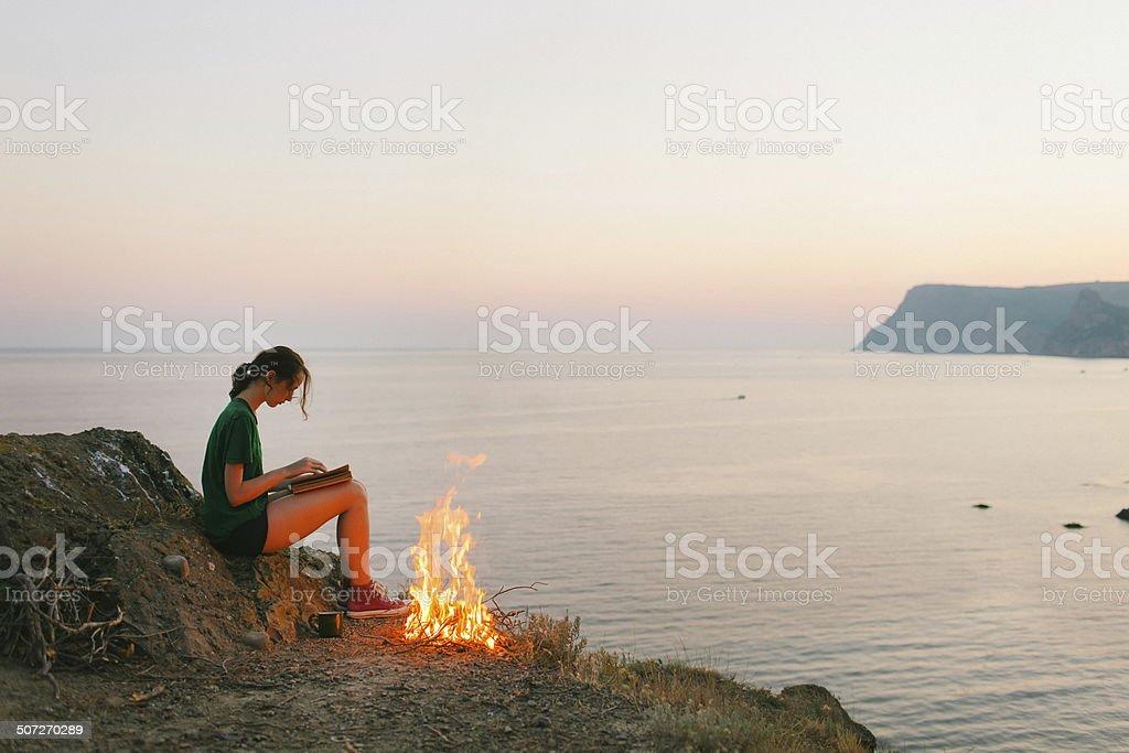 Girl near campfire stock photo