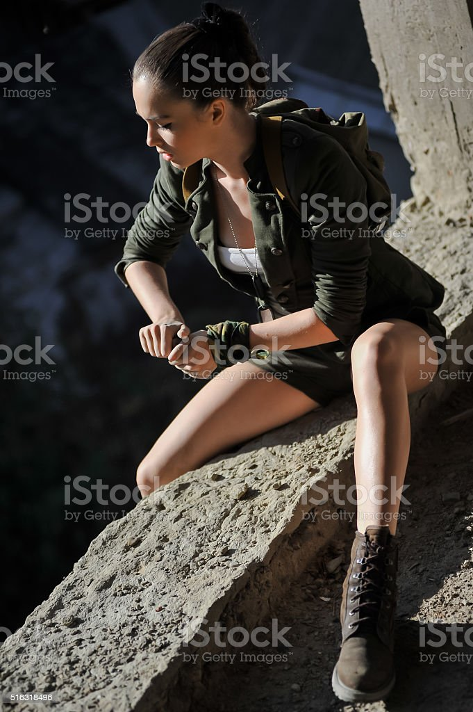 Girl near the brick wall in military style. Lara Croft style. stock photo