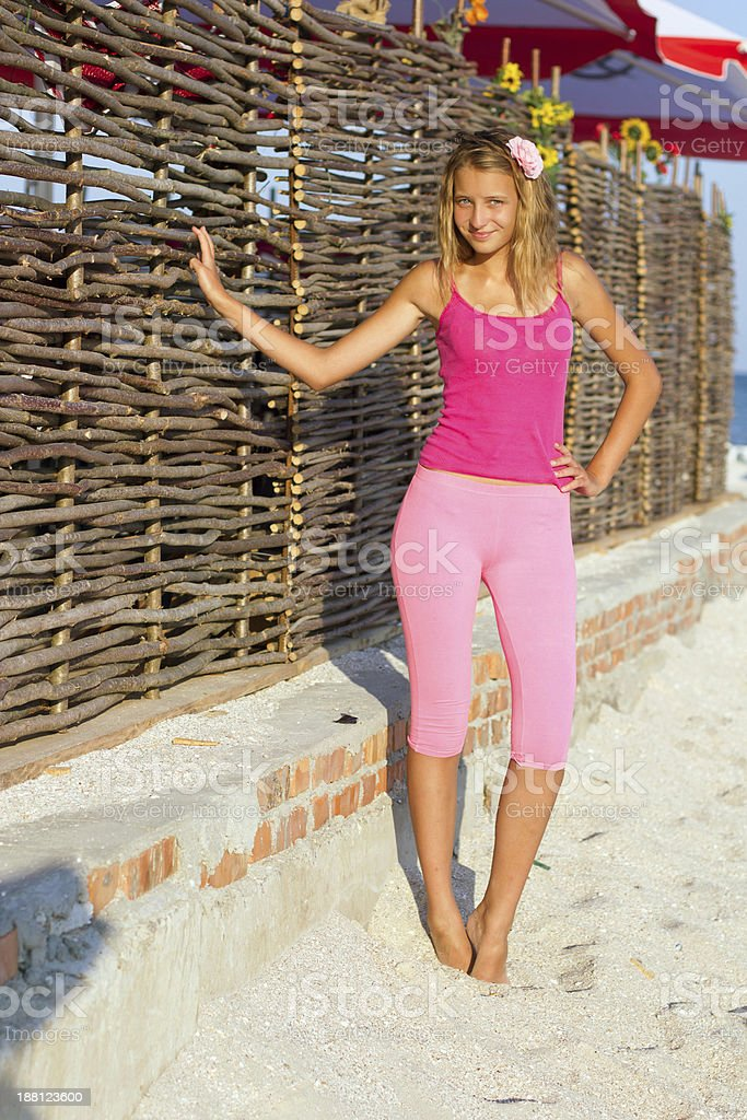 girl near the fence of branches stock photo