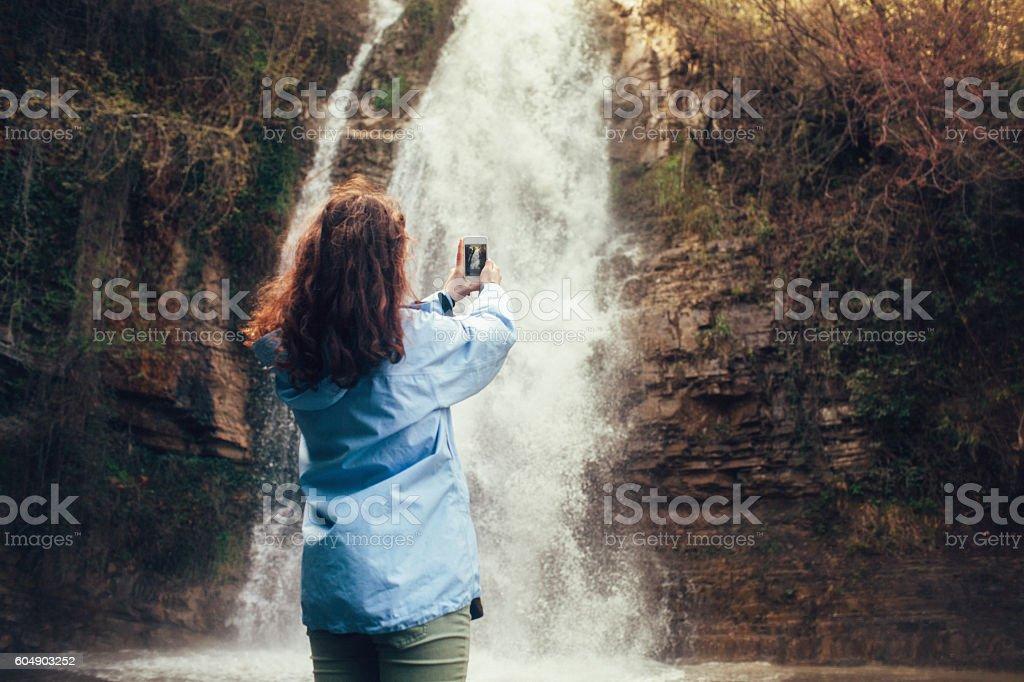 Girl near the waterfall stock photo
