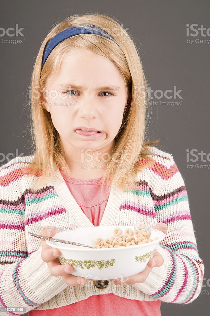 Girl not wanting healthy cereal stock photo