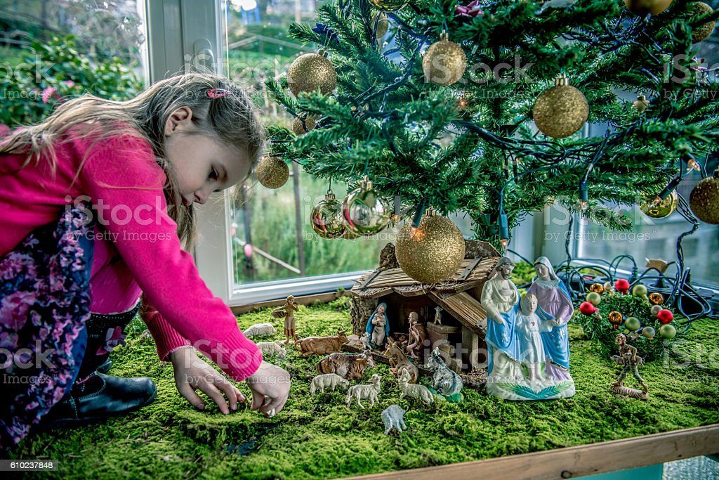 Girl of Four Playing with Figurines at Nativity Scene, Europe stock photo
