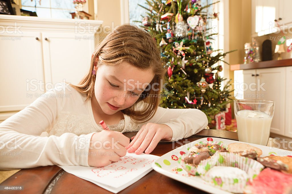 Girl Offering Cookies and Christmas Wish List to Santa stock photo