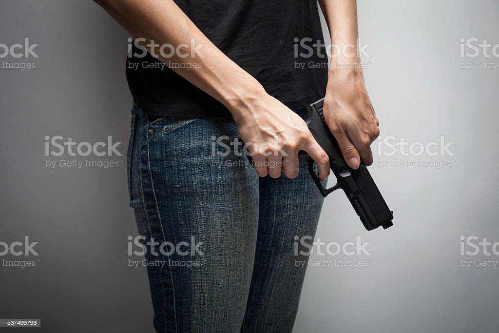 Girl Officer Concealing Weapon stock photo