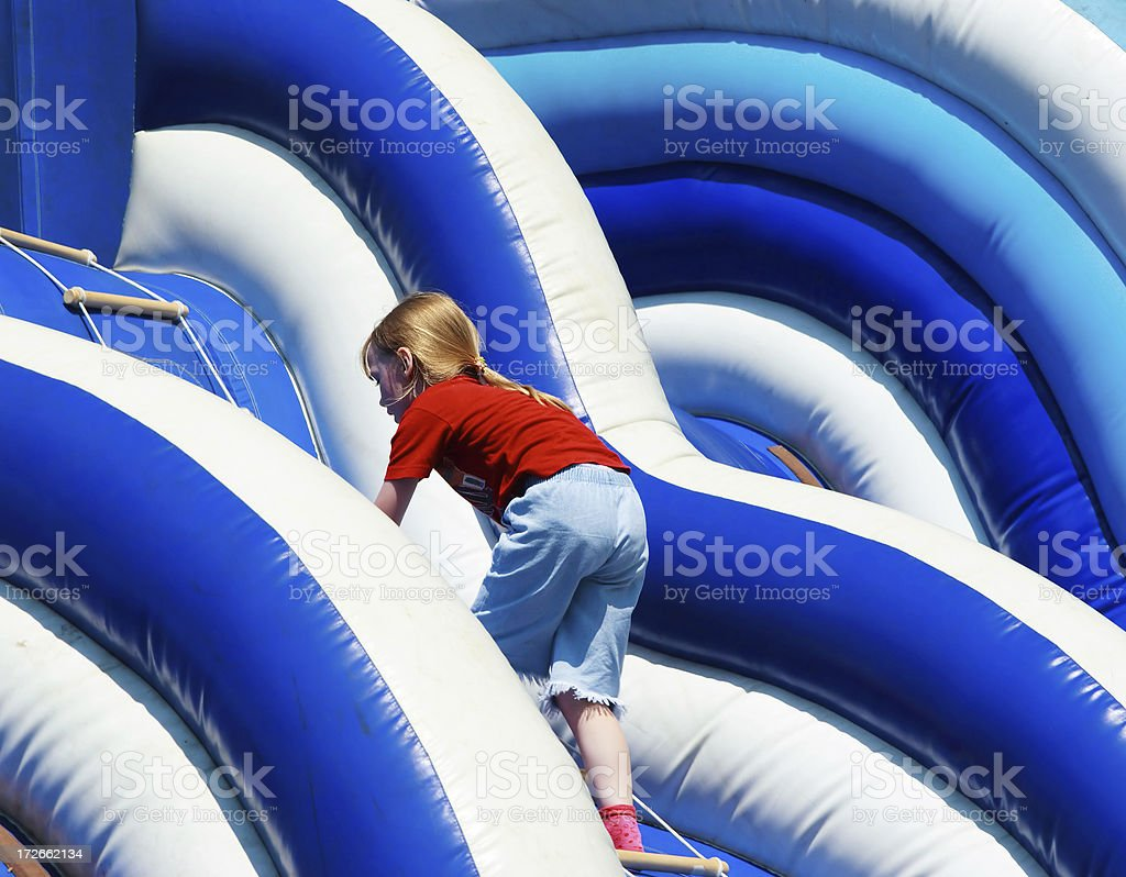 Girl on a blue-coloured inflatable slide royalty-free stock photo