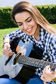 girl on a green meadow playing guitar