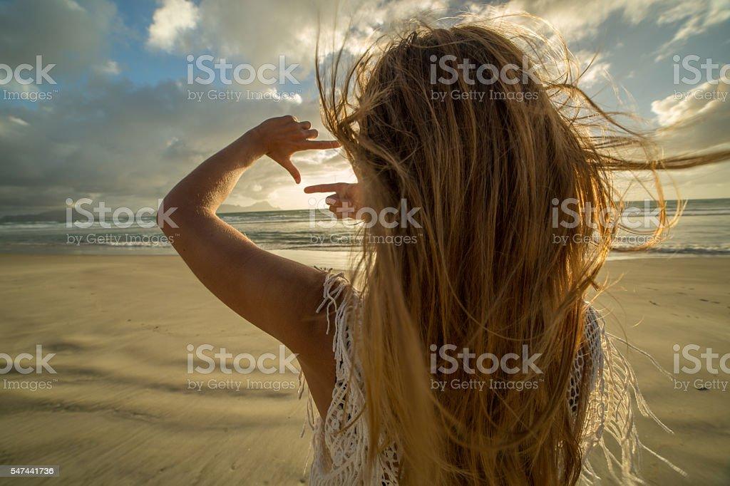 Girl on beach frames sunset into fingers stock photo