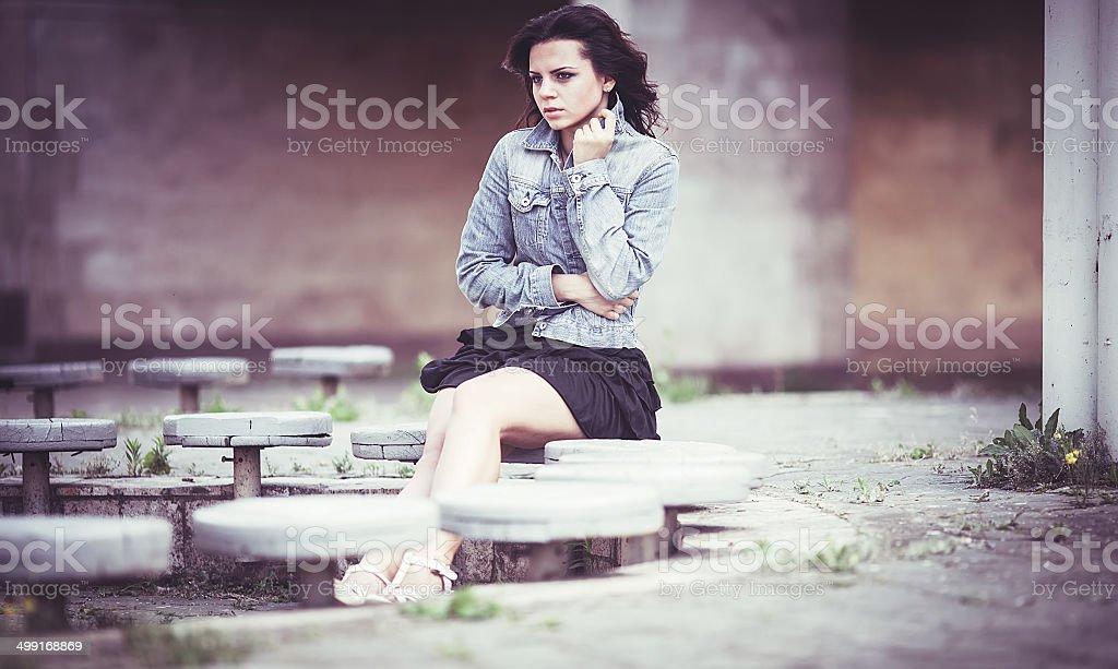 La ragazza sulla panchina in denim jacket foto stock royalty-free