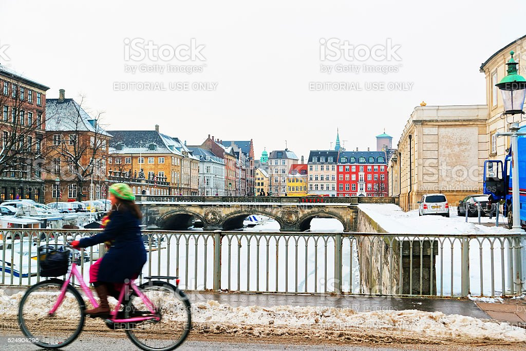 Girl on bicycle passing by the bridge in winter Copenhagen stock photo