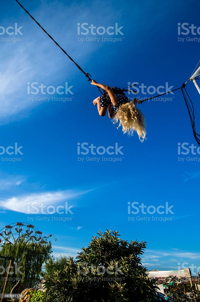 girl on bungee attraction stock photo