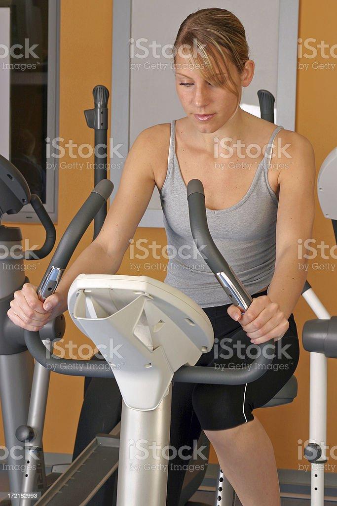 Girl on exercise bike royalty-free stock photo