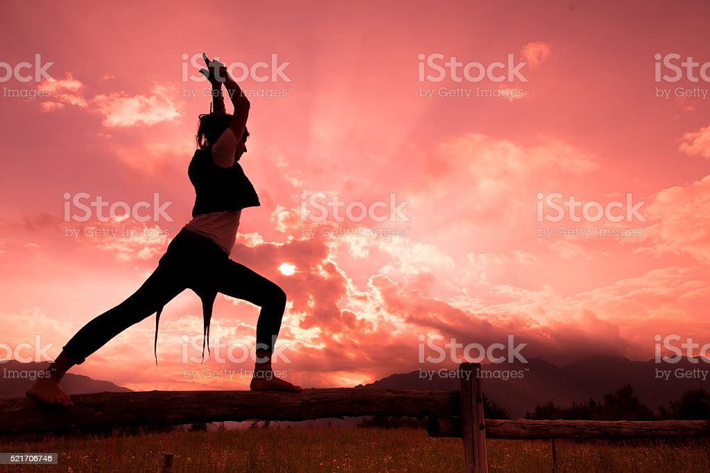 Girl on fence in nature with red sky stock photo