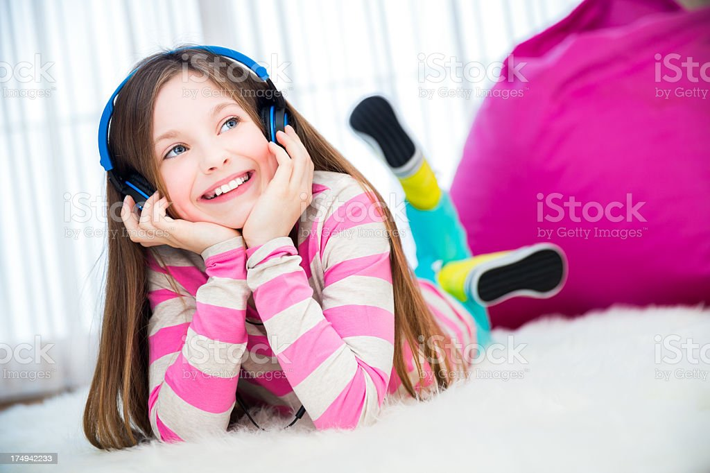 Girl on floor with headphones listening to music royalty-free stock photo