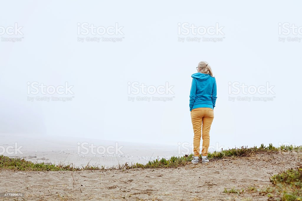 Girl on foggy beach stock photo