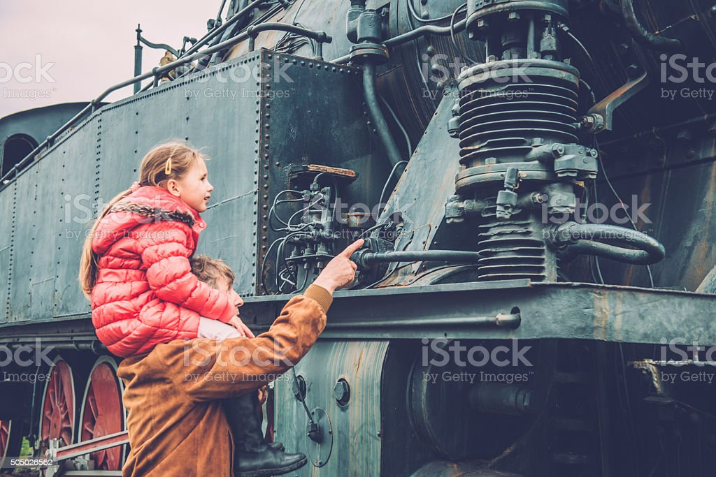 Girl on Grandfather's Shoulders Observing Old Steam Locomotive,  Europe stock photo