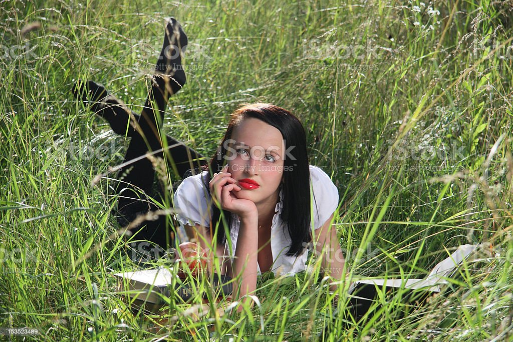 girl on grass, with books. stock photo
