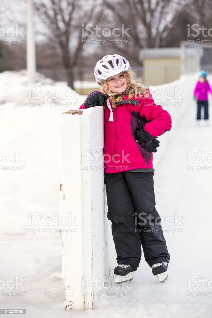 Girl On Hockey Ice Skates Standing at Rink's Edge stock photo