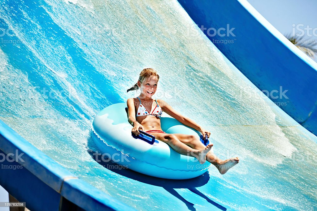 Girl on inflatable ring going down water slide stock photo