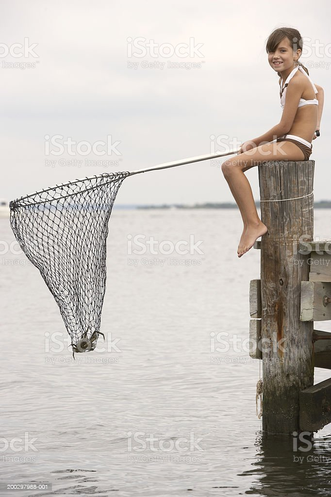 Girl (8-10) on jetty holding fishing net with crab in it, portrait royalty-free stock photo