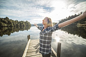 Girl on jetty outstretched arms enjoys freedom and fresh air