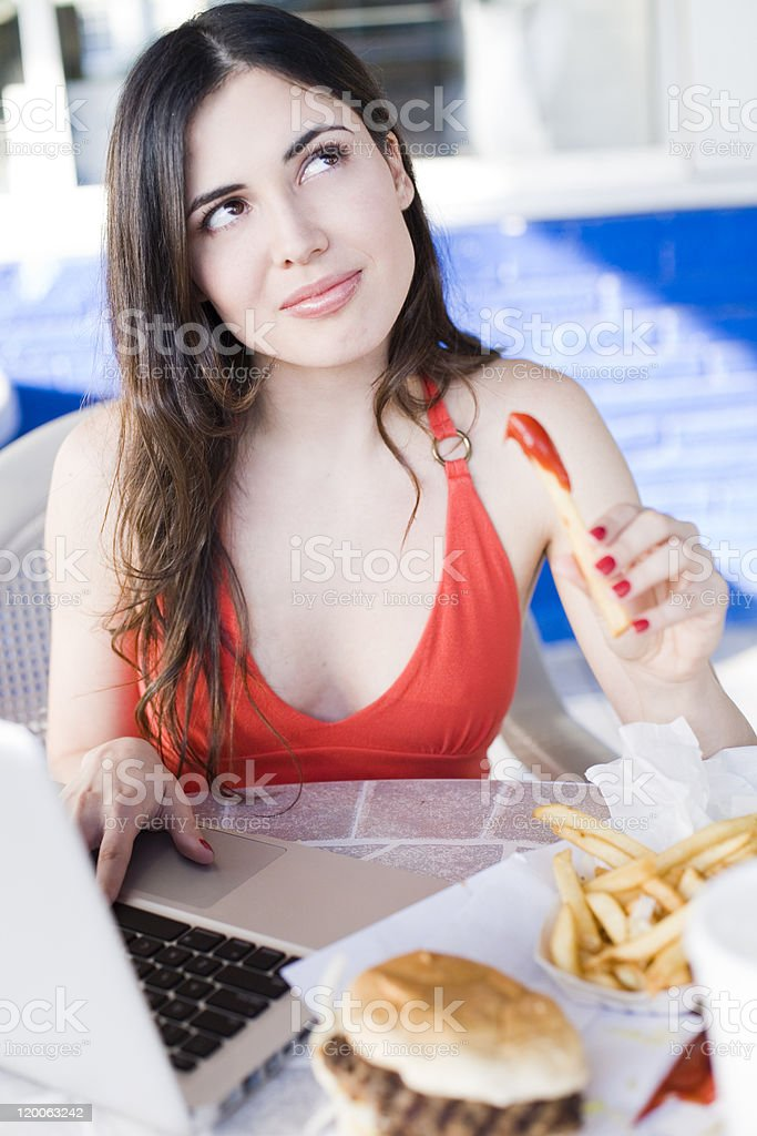 girl on laptop eating fast food royalty-free stock photo