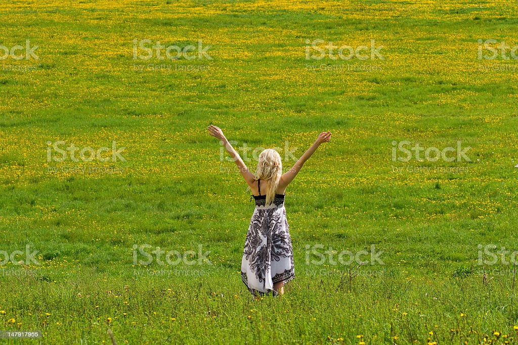 Girl on meadow in spring, arms raised. royalty-free stock photo
