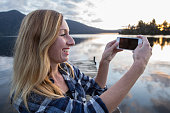 Girl on pier takes picture of landscape with smartphone