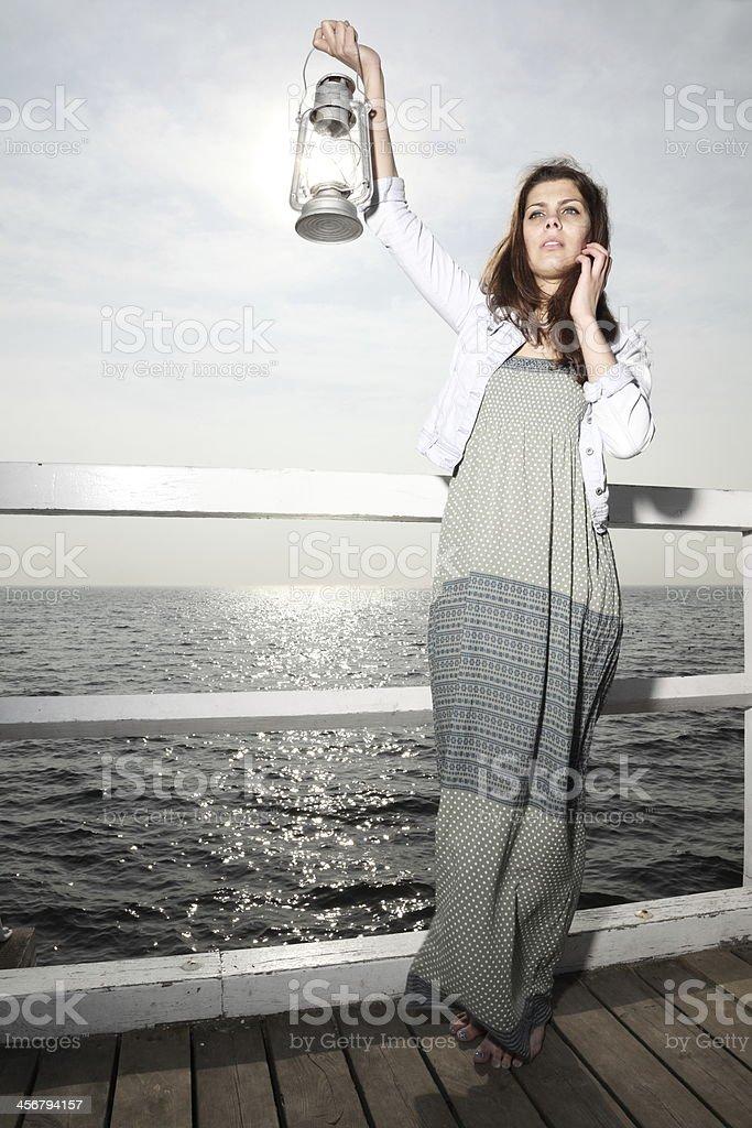 Girl on pier with kerosene lamp stock photo