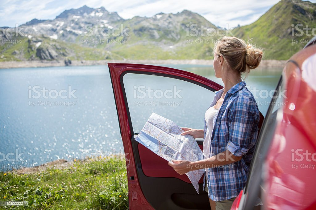 Girl on road trip consulting map-Summer stock photo