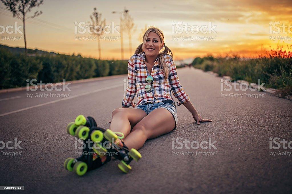 Girl on roller skates in sunset stock photo