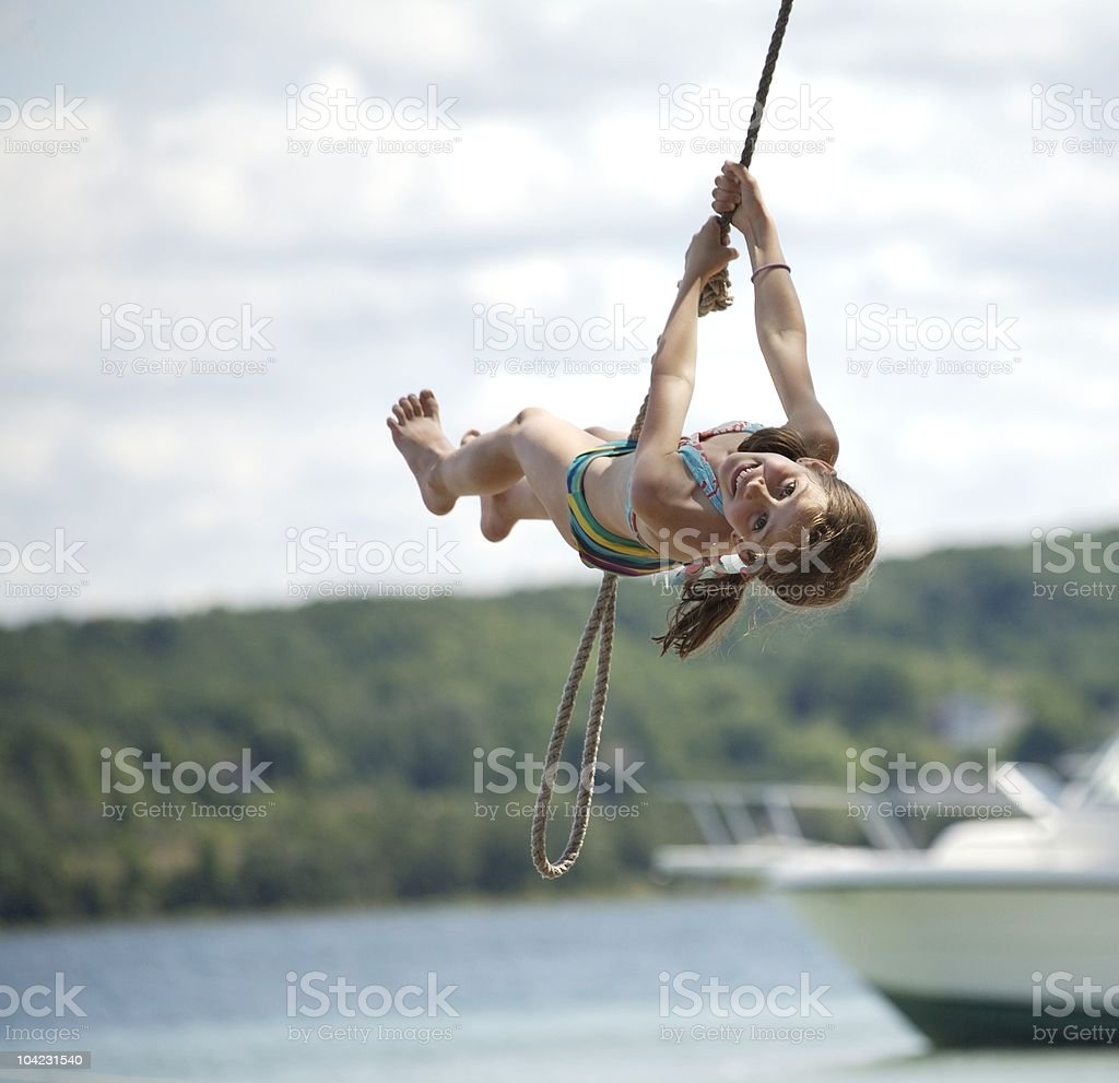Girl on Rope Swing Over the Water stock photo