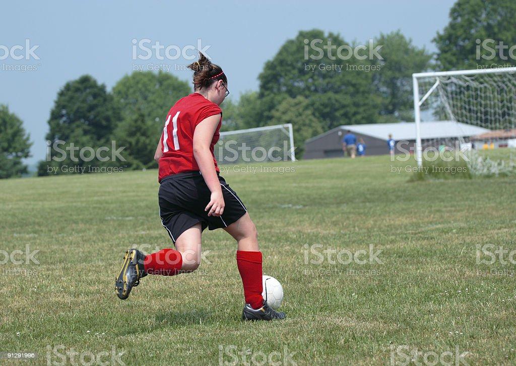 Girl on Soccer Field Kicking Ball royalty-free stock photo