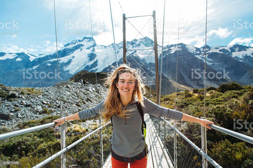 Girl on swing bridge New Zealand stock photo