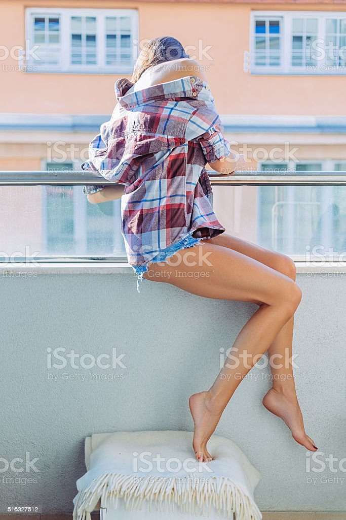 Girl on the balcony looking down on street stock photo