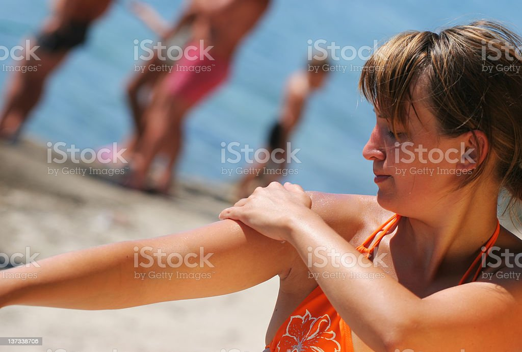 Girl on the beach applying suntan lotion to her shoulders stock photo