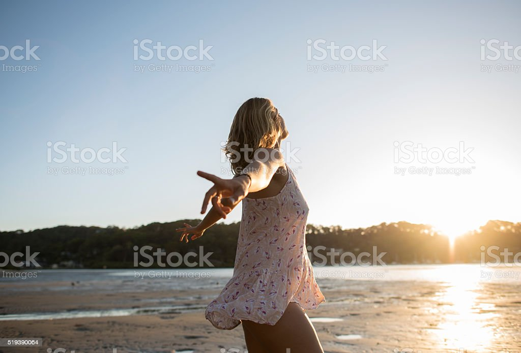 Girl on the beach dancing at sunset with sunflare stock photo