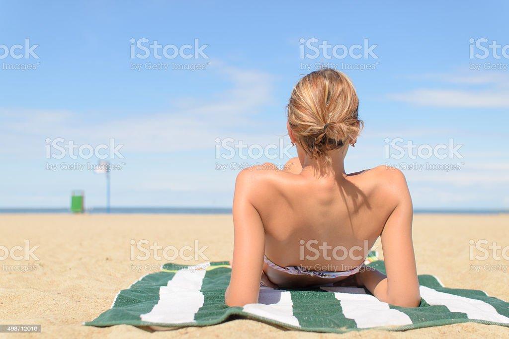 Girl on the beach sunbathing stock photo