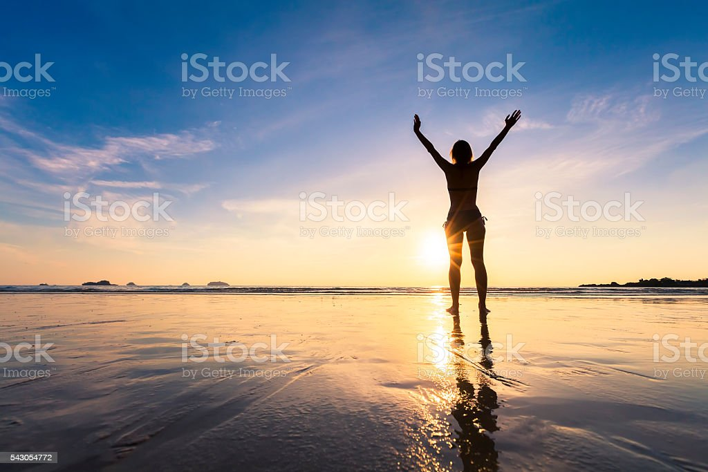 Girl on the beach with feelings of freedom stock photo