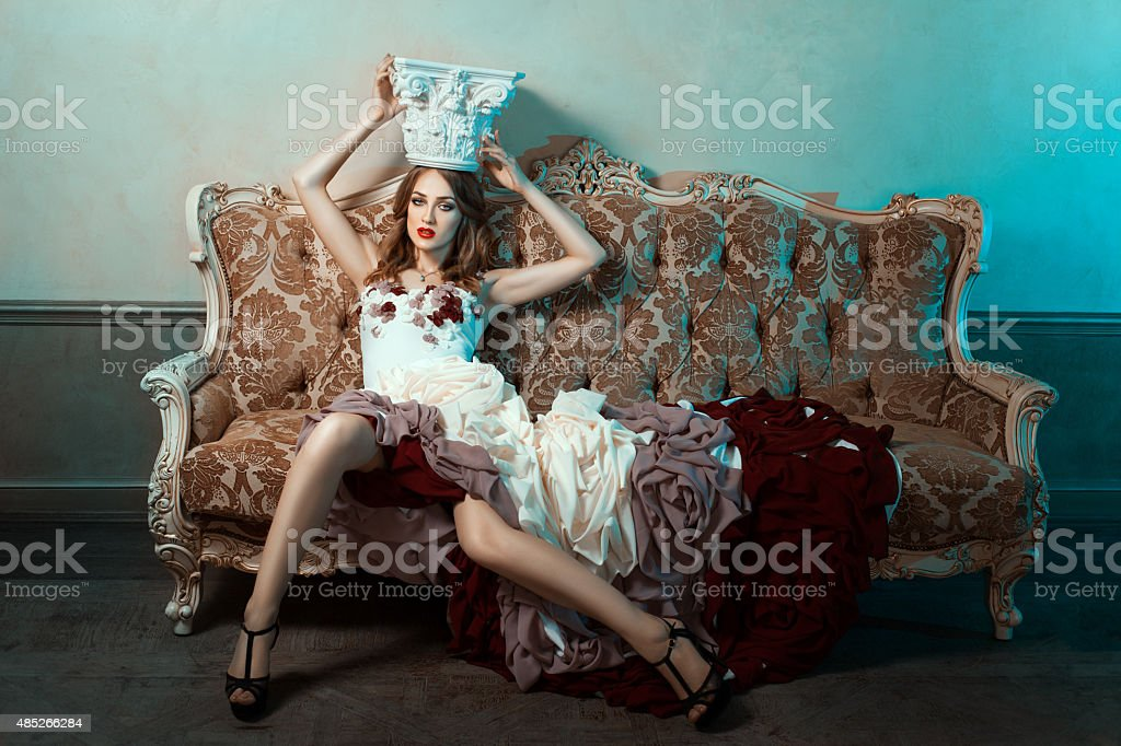Girl on the couch ball gown and trying crown. stock photo