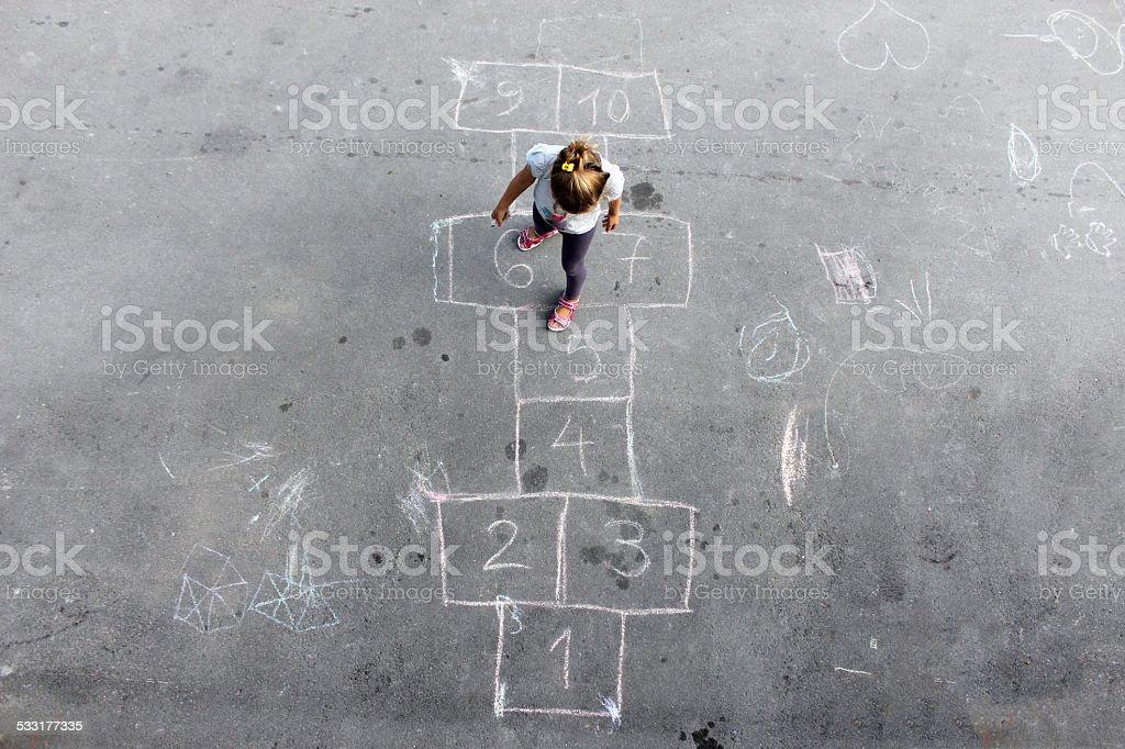 Girl on the hopscotch stock photo