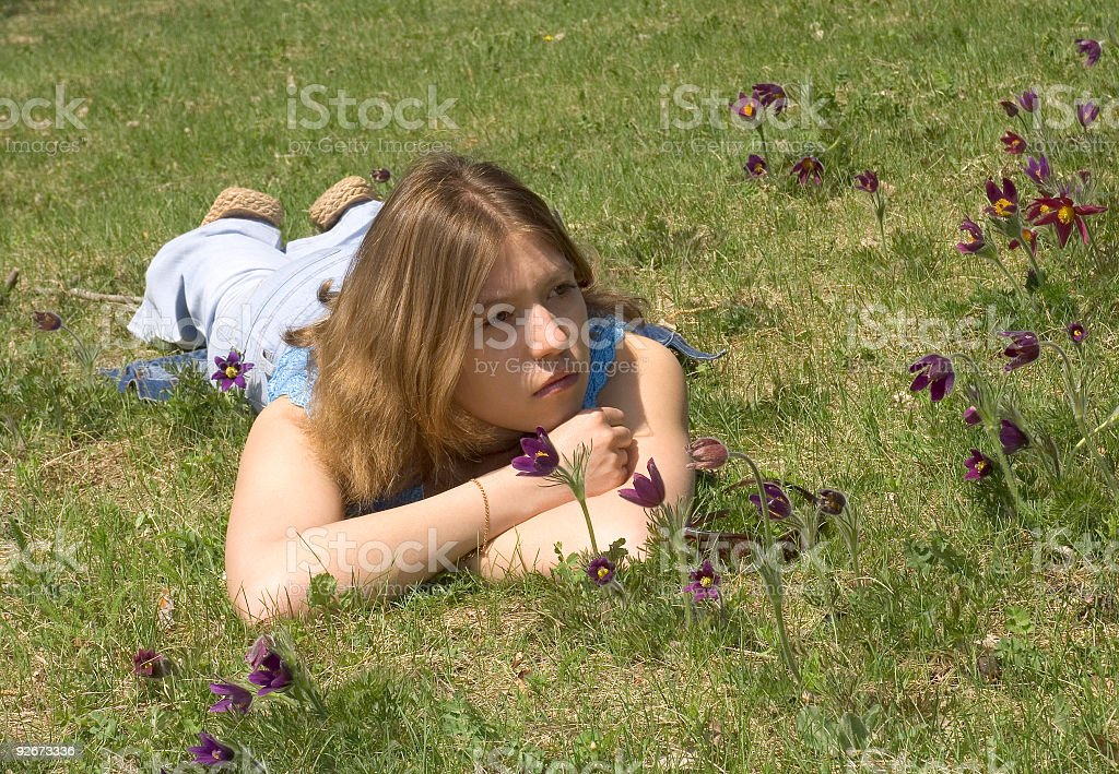 Girl on the lawn with  pasque-flowers royalty-free stock photo
