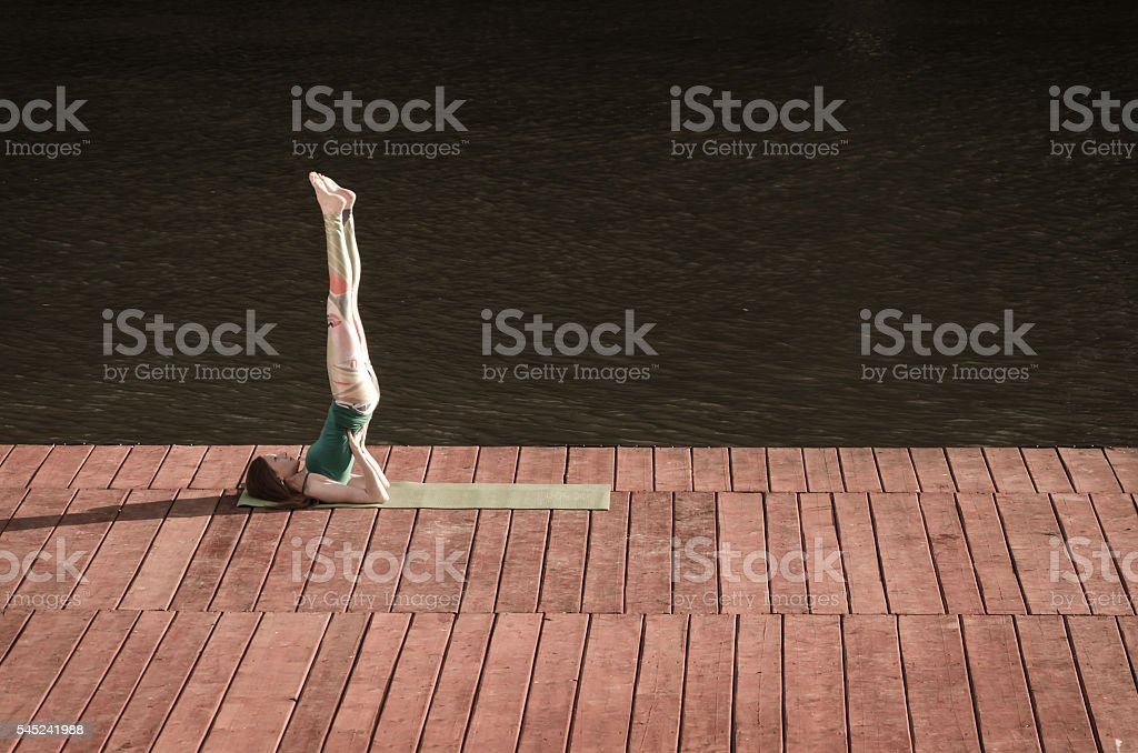 Girl on the raft for practice yoga stock photo