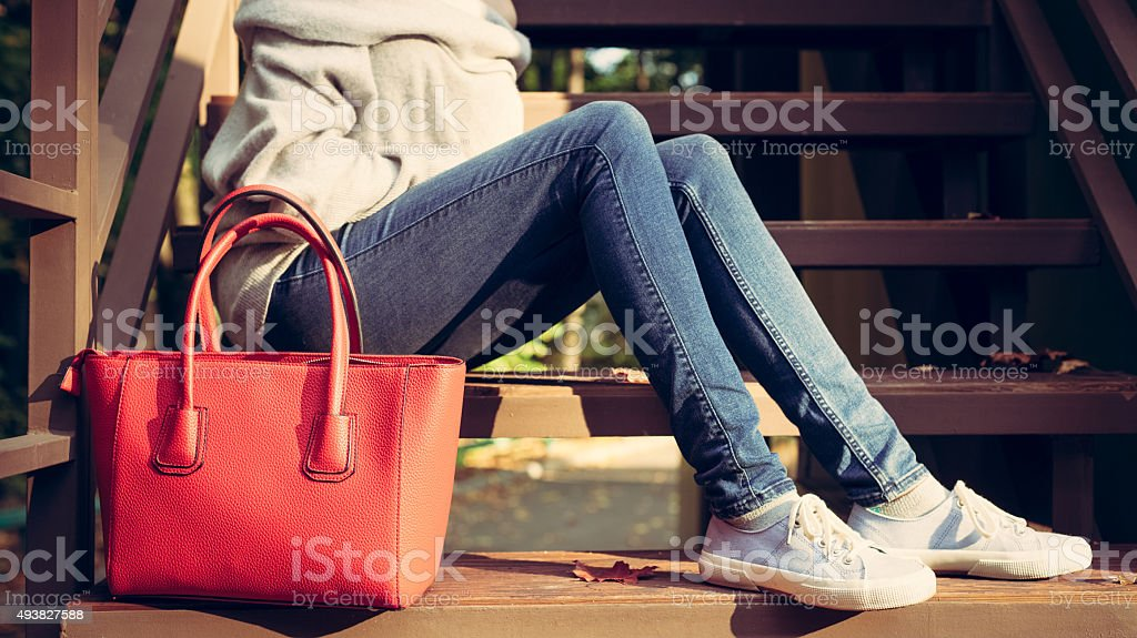 Girl on the stairs with a big red fashionable handbags stock photo