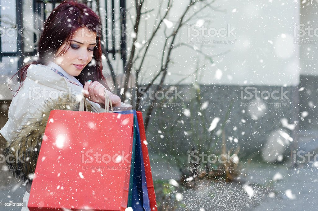 Girl on the street goes shopping with shopping bags stock photo