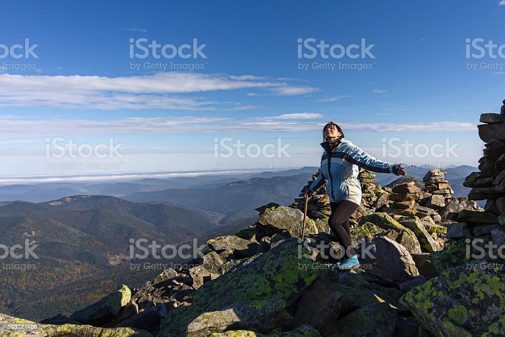 Girl on top of high mountains and open horizon stock photo