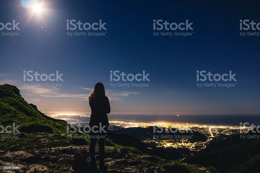 Girl on top of mountain admiring the view stock photo