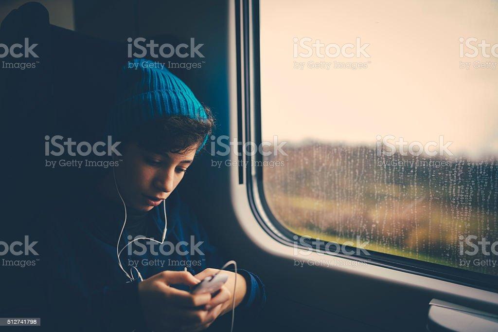Girl on Train using smartphone stock photo