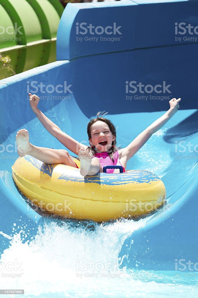 Girl on water slide stock photo