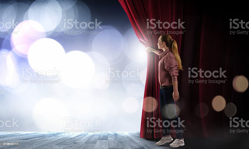 Girl opening curtain stock photo