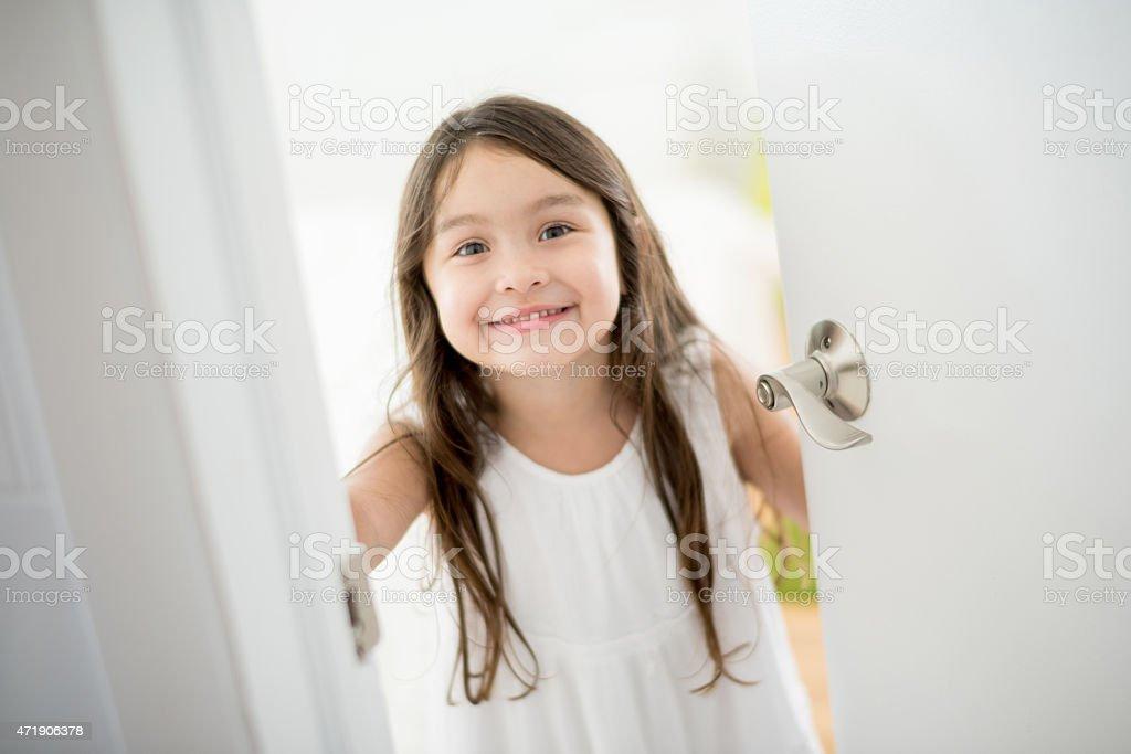 Girl opening the door of her room stock photo